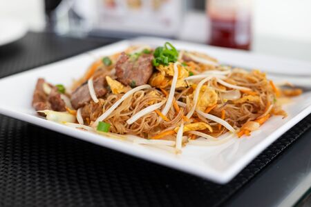 noodles with meat on white plate in restaurant Reklamní fotografie