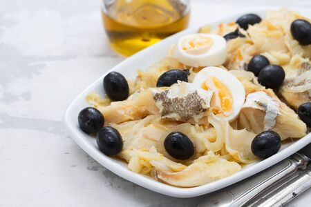 cod fish with onion, olives, eggs and olive oil on dish on ceramic background