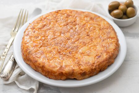 typical spanish food Tortilla with smoked meat and potato on white dish Zdjęcie Seryjne - 130755772