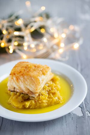 cod fish with mashed potato and olive oil on white dish