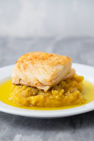 cod fish with mashed potato and olive oil on white dish Imagens