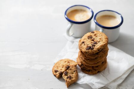 coffee and cookies with chocolate chips on ceramic background