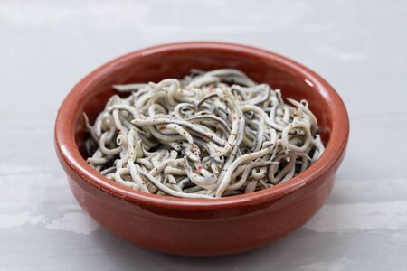 Traditional Spanish food. Gulas with oil in ceramic dish. Stock Photo