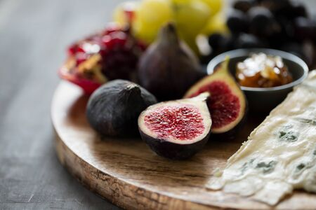 figs with cheese, grapes and honey on wooden board