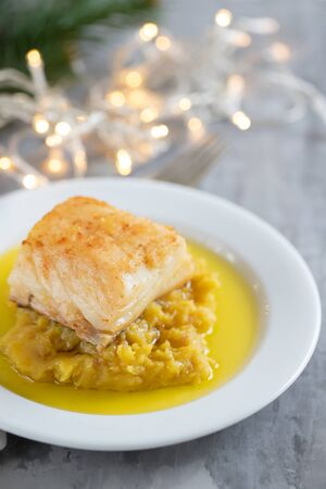 cod fish with sweet potato and olive oil on white dish