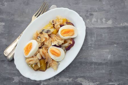 cod fish with sweet potato and boiled egg on white dish on ceramic background