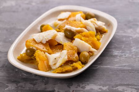 cod fish with sweet potato and olives on dish on ceramic background Stockfoto
