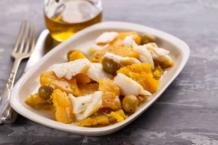 cod fish with sweet potato and olives on dish on ceramic background Imagens