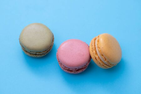 delicious colorful macaroons on blue paper background 写真素材