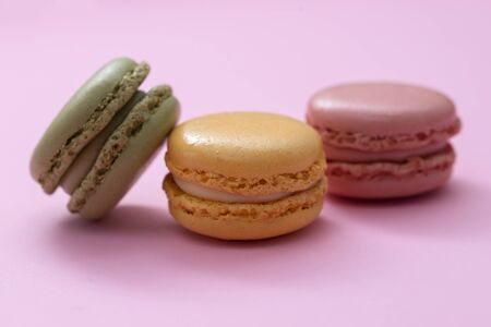 delicious colorful macaroons on pink paper background