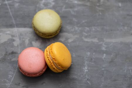 delicious colorful macaroons on ceramic background