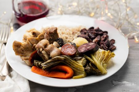 typical portuguese dish boiled meat, smoked sausages, vegetables and rice on white plate