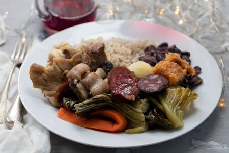 typical portuguese dish boiled meat, smoked sausages, vegetables and rice on white plate Imagens