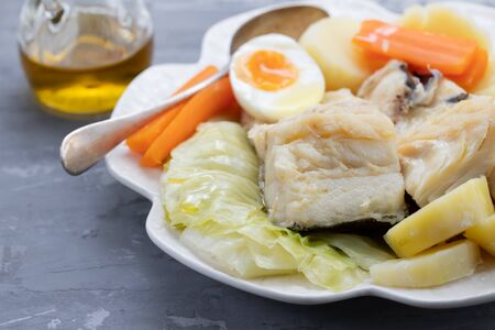 boiled fish with vegetables and boiled egg on white plate Imagens