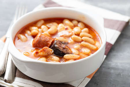 typical spanish dish fabada, beands with smoked sausages and meat on white bowl
