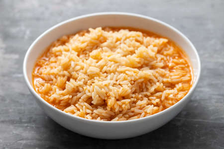 boiled rice with tomato in bowl on ceramic background