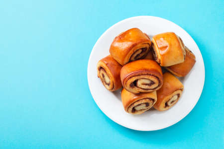 buns with cinnamon on white plate on blue background