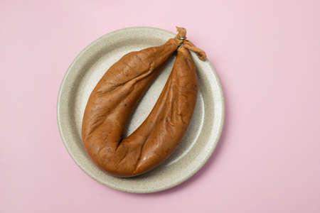 typical portuguese smoked sausage Farinheira on the dish on pink background