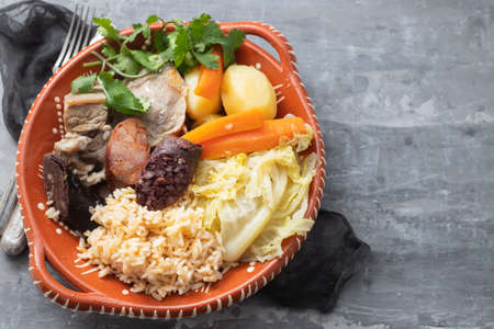 typical portuguese dish boiled meat, smoked sausages and vegetables on ceramic dish