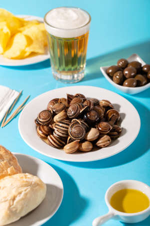 boiled snails with bear, bread, olives and potato chips on blue Imagens