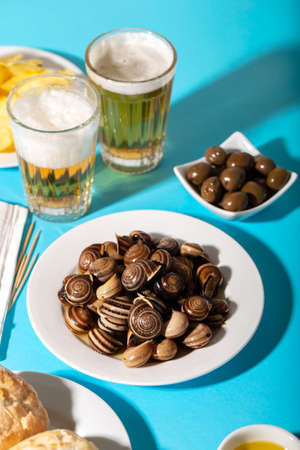 boiled snails with bear, bread, olives and potato chips on blue
