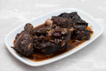 Old goat meat dish Chanfana, traditional portuguese, roasted in pans on grey ceramic background Imagens
