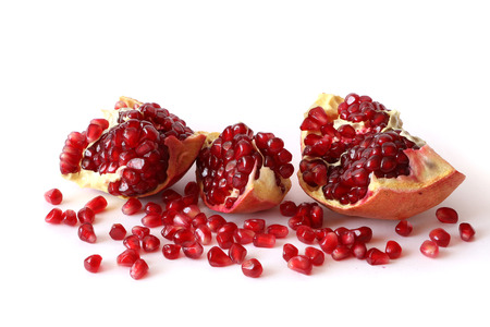 Red Background of Grain Red Grenades. Big Ripe Red Granets or Garnets. Fruits of Red Ripe Pomegranate on the White Background. Vegetarian Concept, Organic Vitamins. Organic and Benefit Garnet Fruit.