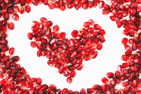 Heart shaped pomegranate seeds on white background. Love, Valentines day and healthy life concept, flat lay top view. Pomegranate seeds in a shape of heart. Red heart isolated on the white background Stock Photo