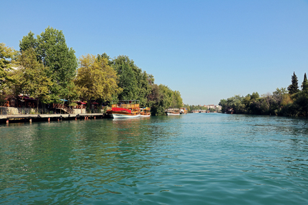 MANAVGAT, TURKEY - JUNY 2017: Boats on Manavgat river on Juny, 2017 in Manavgat, Turkey. Manavgat is famous among tourists for sandy beaches, long rivers and the waterfall, mountains and forests. Editorial