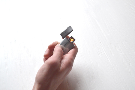 Man holding a usb lighter in his hands.