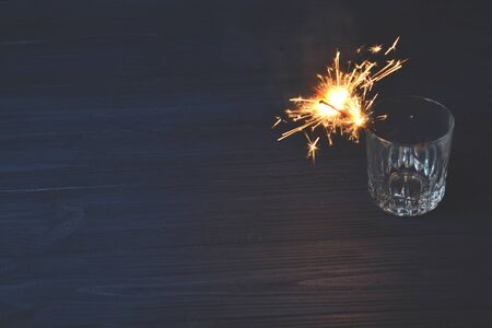 Sparkler in the glass. Holidays lights. New Year celebration. Stock Photo