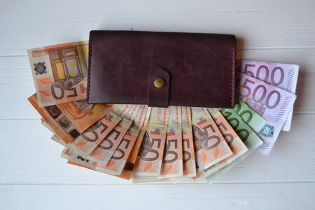 Euro money banknotes and wallet on the white wooden desk. Business money background.