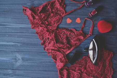 Woman's accessories on the wooden table. Red lace lingerie.