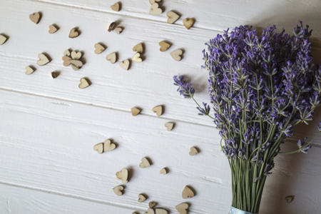 Bouquet of lavender and wooden love hearts on a white wooden table. Beautiful romantic background with copy space.