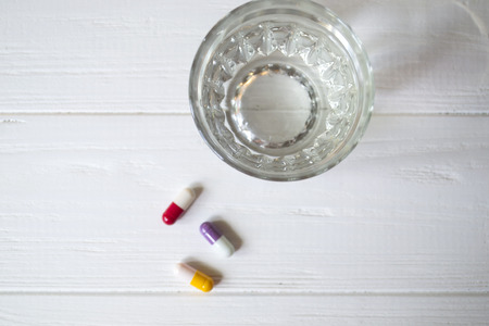 A tablets and a glass of water on a white table.