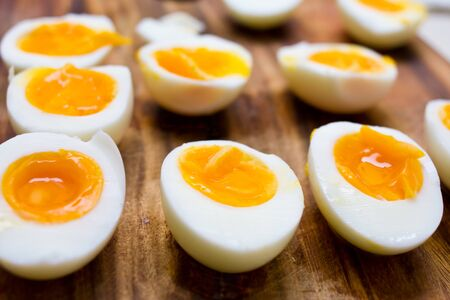 Hard boiled eggs, sliced in halves on wooden background 스톡 콘텐츠