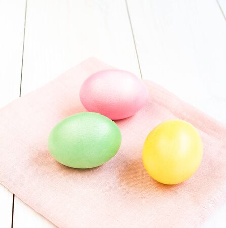 Colored boiled Easter eggs on white wooden background photo