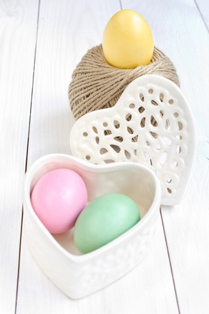 Easter egg in a heart shaped box and a rolling ball of hemp rope on wooden background photo