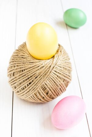 Easter egg and rolling ball of hemp rope on wooden background photo