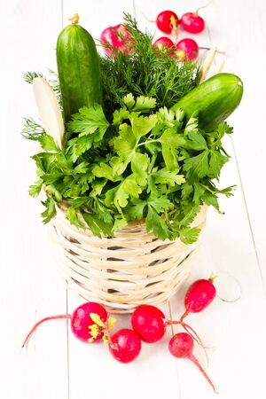 A bouquet of fresh different vegetables in a bowl wicker basket on white wooden background photo