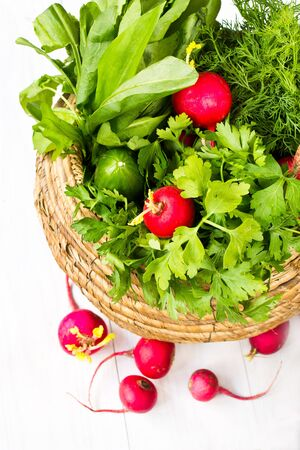 A bunch of fresh different vegetables in a bowl wicker basket on white wooden background Stock Photo - 19654552