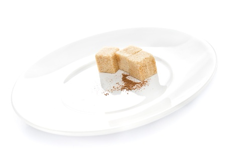 fine cane: Cane cube sugar and dark chocolate powder on a  plate on white background