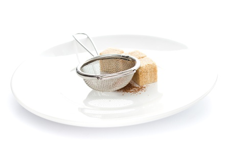 fine cane: Metal sieve and cane sugar chocolate powdered on a  plate isolated on white background