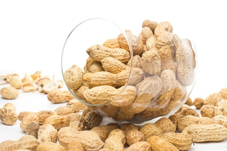 earthnut: Raw shelled big peanuts in a glass on white background, closeup  Stock Photo