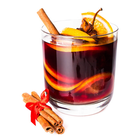 Cup of Hot red mulled wine isolated on white background with christmas spices, orange slice, anise and cinnamon sticks, close up.