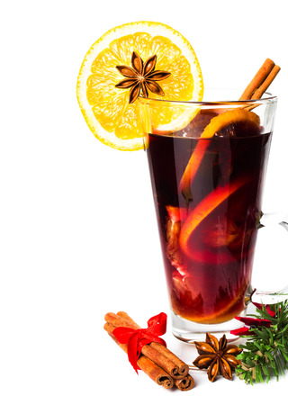 Red Hot Christmas mulled wine with spices, orange slice, anise and cinnamon sticks  isolated on white background, closeup.