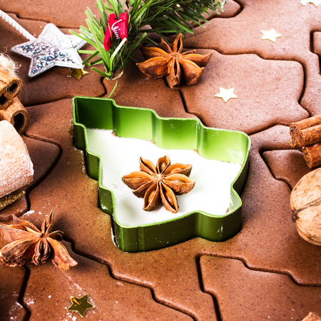 festive food: Christmas  background with Gingerbread baking, cookie cutters, spices and nuts. Christmas festive food, top view, closeup. Stock Photo