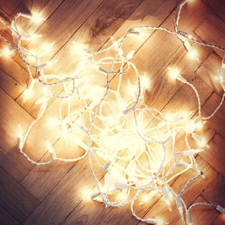 Christmas card lights garland on a old antique wooden parquet floor, photo