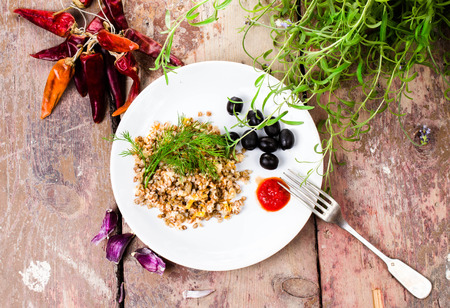 Boiled buckwheat, pepper, black olives and herbs on white plate on  vintage dark wood background.  photo