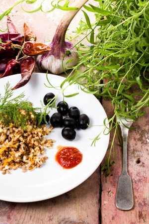 Buckwheat, pepper, black olives and herbs in white dish on  vintage dark wood background.  photo
